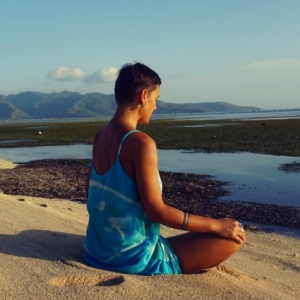 Woman meditating sitting at the Beach